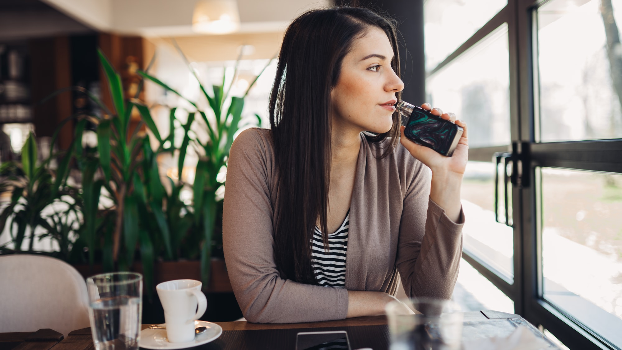 a young woman vaping in public